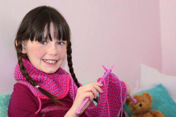 Smiling little girl knitting at home with a teddy bear.