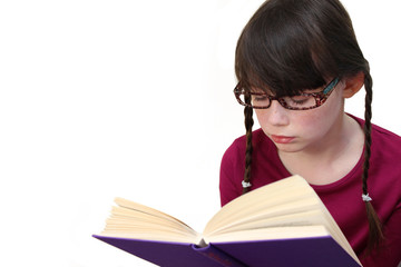 Little girl wearing glasses reading a book close up on white bac