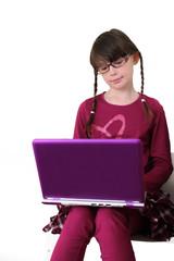 Little girl wearing glasses using laptop on white background.