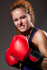 Beautiful girl with red boxing gloves, aggressive and looking at
