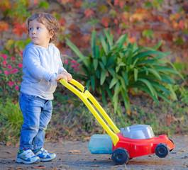 Bimbo gioca a tagliare l'erba