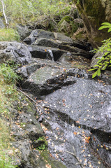 Waterfall flowing over dark rocks
