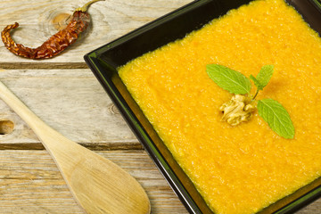 Pumpkin puree on a black plate decorated with mint, walnut and c
