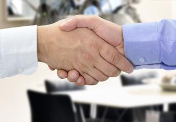 Hände beim Vertragsabschluss vor Konferenztisch