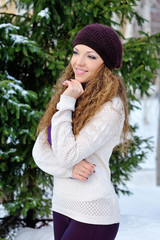 beautiful girl in a purple knitted winter hat and scarf and knit