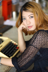 attractive asian woman using typewriter in the cafe
