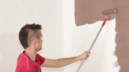 Man with paint roller painting interior.