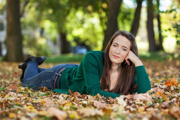 Woman lying in autumnal park