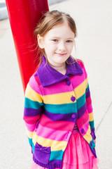 Outdoor portrait of a cute little girl in a street