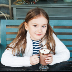 Cute little girl drinking hot chocolate in a cafe