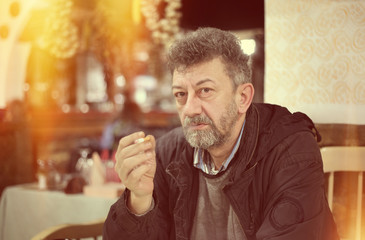 Adult man with beard smoking cigarette vintage look of photo