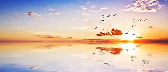 paisaje panoramico de una amanecer con las nubes en el agua
