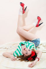 Pretty pinup lady in shorts and striped blouse