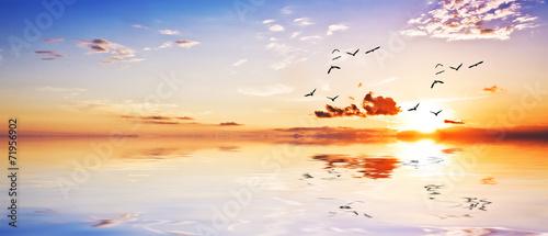 Fotobehang Een Hoekje om te Dromen paisaje panoramico de una amanecer con las nubes en el agua