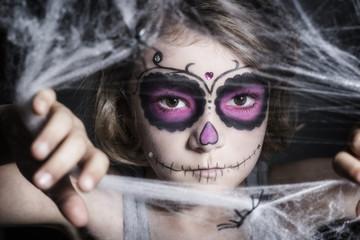kleines Mädchen mit Sugar Skull Make up, hinter Spinnweben