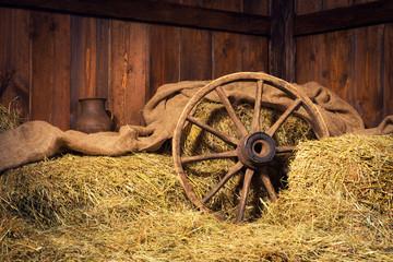 Interior of a rural farm - hay, wheel, pitcher.
