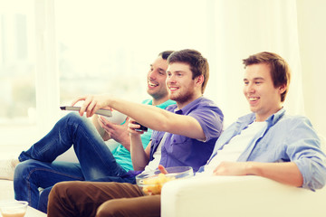 smiling friends with remote control at home