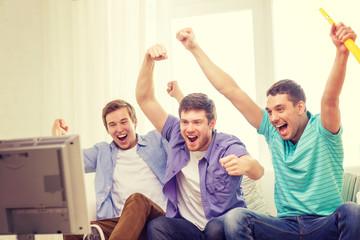 happy male friends with vuvuzela watching sports