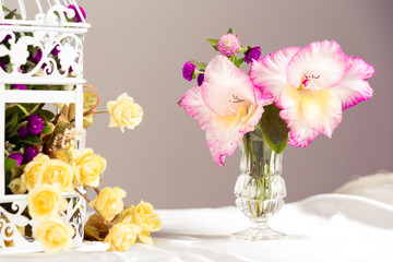Orchids in glass vase and roses.