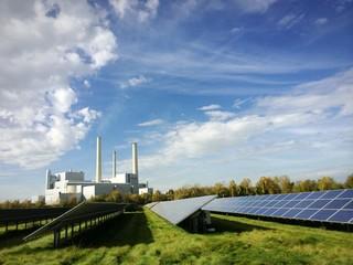 Solaranlage und Heizkraftwerk unter blauem Himmel