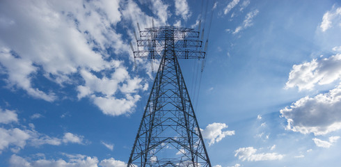 Centered Electric tower over blue sky and clouds