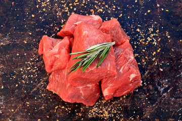Raw beef cubes on brown rustic background