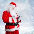 Weihnachtsmann mit Tablet in Winterlandschaft