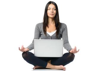 Hübsche Frau mit einem Laptop bei der Meditation