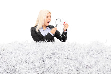 Shocked woman looking at a pile of shredded paper