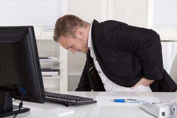 Business Mann mit Schmerzen im Büro: Rückenschmerzen