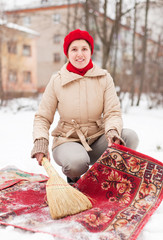 woman in  cap cleans carpet with snow