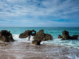 Junge Frau steigt in die Wellen am Meer