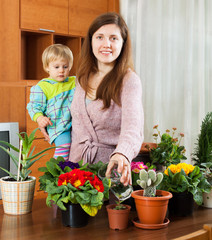 Mother and  toddler are transplanting and watered potted flowers