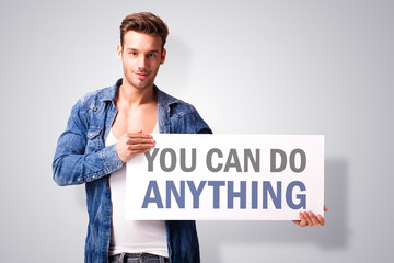 "handsome  man with a signboard with ""you can do anything"""
