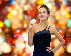 smiling woman in evening dress holding credit card