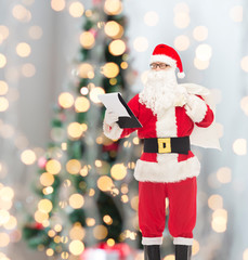 man in costume of santa claus with notepad and bag
