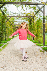 Cute little girl spinning around in a beautiful park