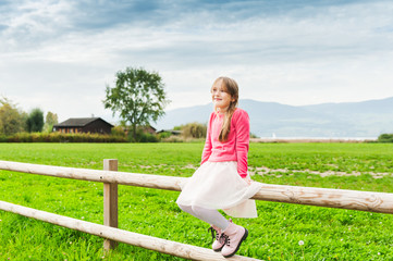 Cute little girl sitting on a fence in a countryside