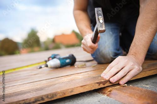 Handyman installing wooden flooring - 71965962