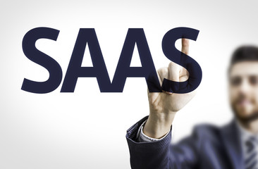 Business man pointing to transparent board with text: SAAS