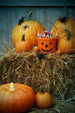 Bucket filled with halloween candy and pumpkins
