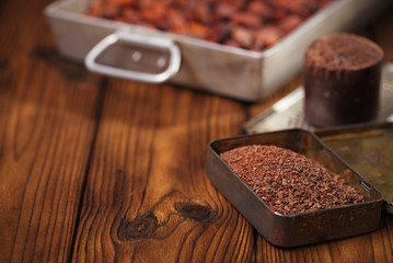 grated dark chocolate in tin with cocoa beans and solid piece in