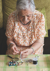 Elderly woman making one necklace