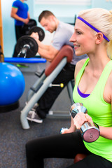 Woman in gym training with dumb bells