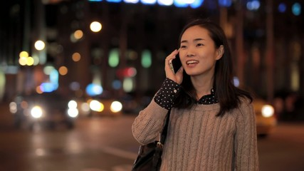 Young Asian Woman talking on cellphone at night