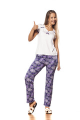 girl with long hair in pajamas and slippers showing thumbs up