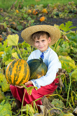 Smiling boy holding  big yellow pumpkin in hands