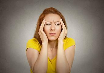 Headshot woman suffering from headache on grey background