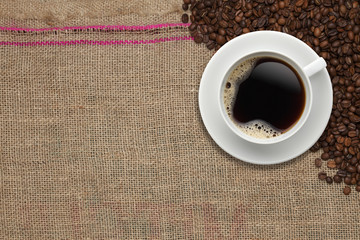Coffee beans and Coffee cup on a jute background
