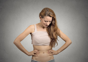 girl looks at her abdomen with concerned face expression
